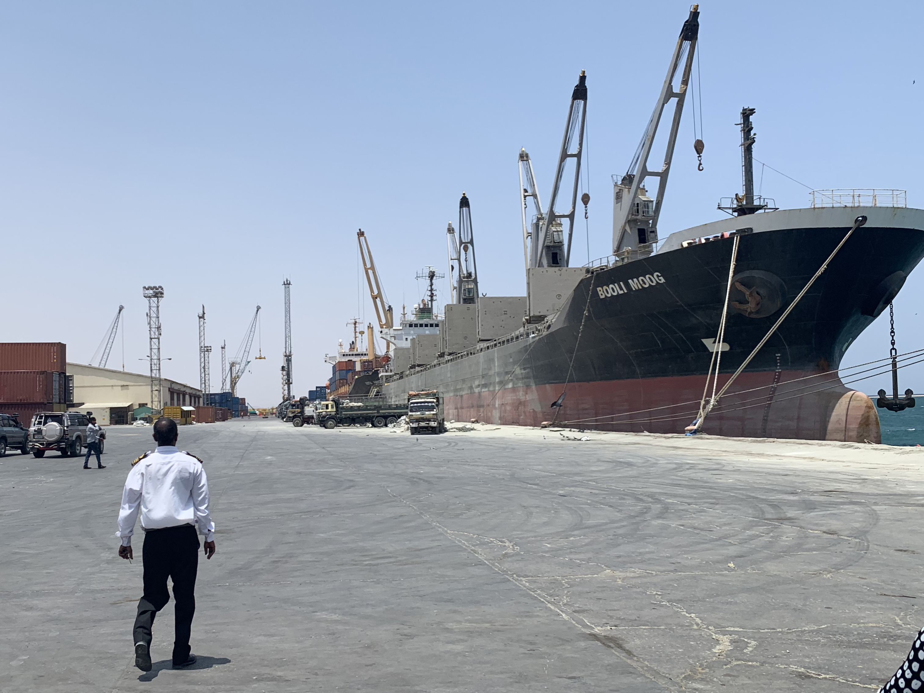 Captain Hersi Jama Hassan, standing at the end of the dock, points out where the UAE has begun extending the port to dramatically increase its capacity. Photo: Ray Hartley